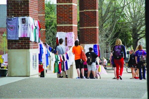 People stop to read messages written by students on shirts hung on clotheslines at the UC plaza. The messages depict stories of sexual abuse, proclamations of hope and confessions to help raise awareness for victims of violence. Stephen Kemp | Staff Photographer