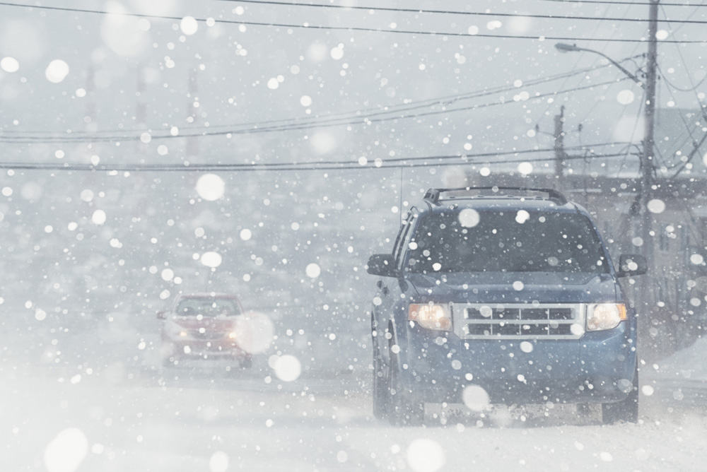 Car drives through snow weather conditions | Getty Images